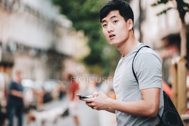 Seitenansicht eines unsicheren asiatischen Mannes im T-Shirt, der auf einer belebten Straße herumsurft und sich umsieht — Stockfoto