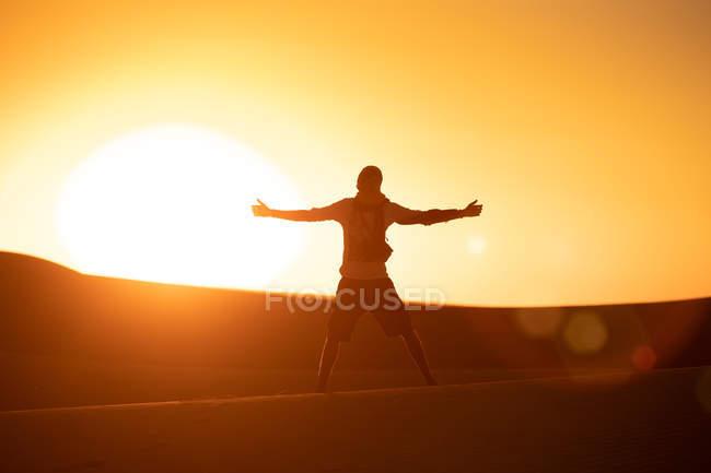 Vue de dos d'un touriste méconnaissable aux bras tendus, debout sur un ciel ensoleillé et sans nuages dans le désert — Photo de stock