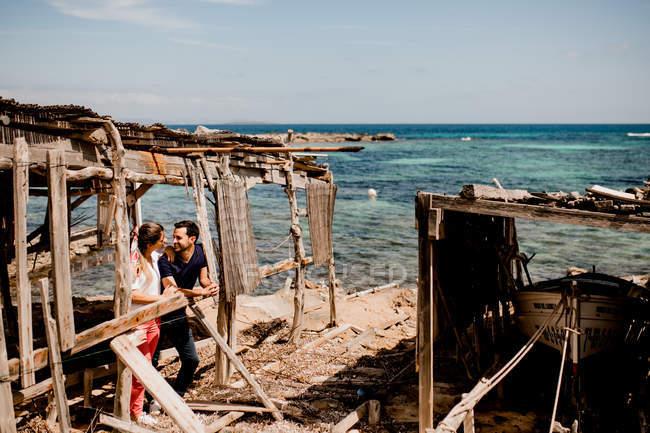 Uomo e donna innamorati che si abbracciano sulla riva sotto un baldacchino di legno squallido in estate e si guardano — Foto stock