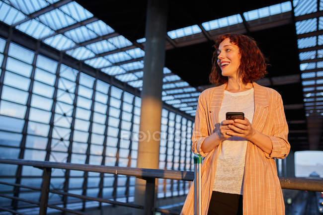 Souriant jeune femme navigation téléphone à la station — Photo de stock