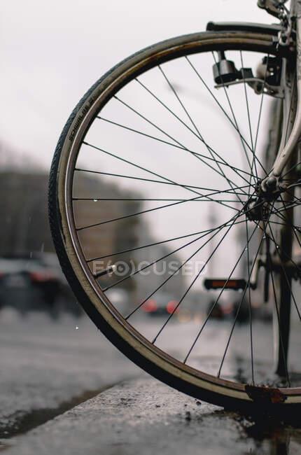 З-під колеса з металевими спицями повернув і зупинився на мокрій дорозі в сірий дощовий день — стокове фото