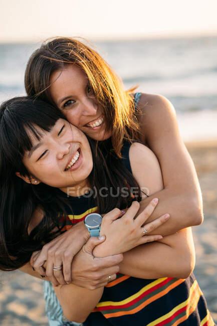 Two beautiful multi ethnic women hugging on the beach — Stock Photo