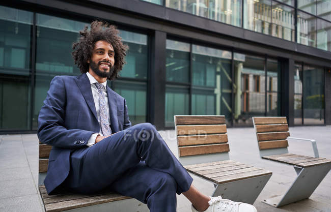 Optimistic and merry African American entrepreneur with beard sitting on bench with crossed legs and looking away — Stock Photo