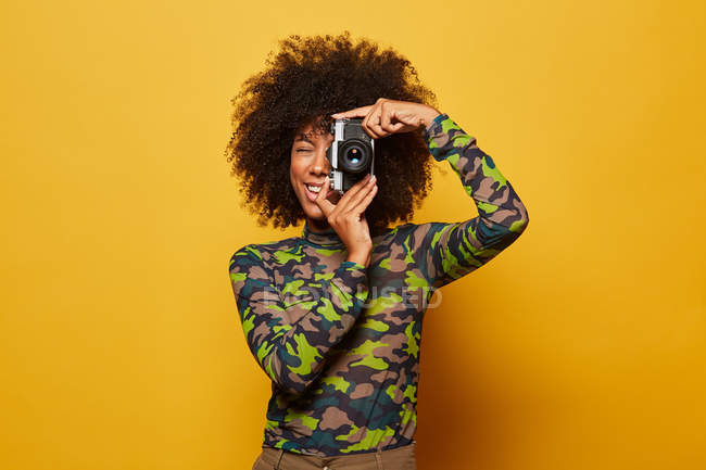Professional cheerful female photographer taking picture with stylish photo camera while standing at yellow background — Stock Photo