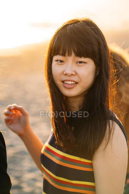 Ritratto colorato di una bella ragazza asiatica sulla spiaggia con il sole che splende sui suoi capelli — Foto stock
