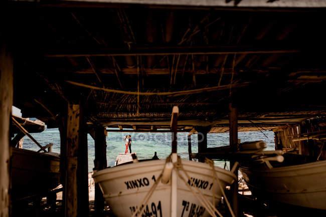 Bateau blanc amarré à terre sur la plage au quai en été avec couple à distance sur jetée — Photo de stock