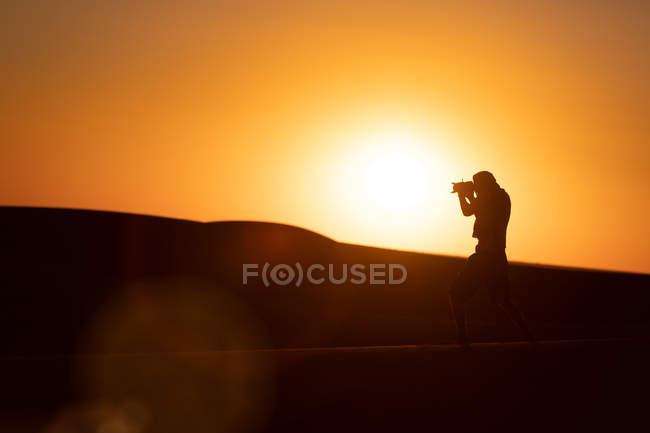 Silhouette inreconnaissable d'un voyageur photographiant des dunes debout sur du sable dans un désert étonnant — Photo de stock