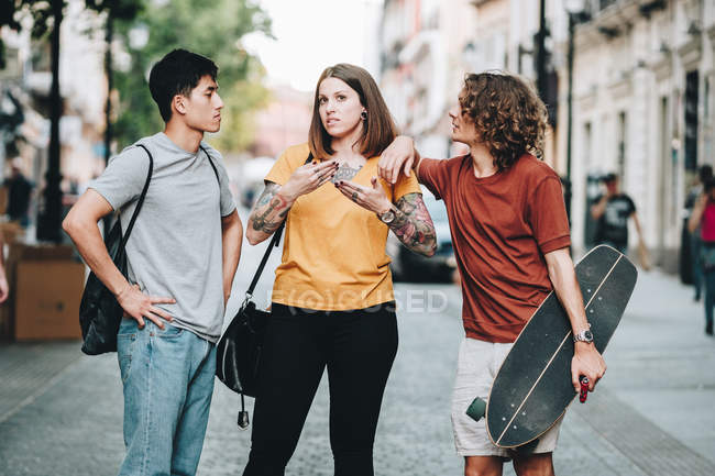 Multiethnic people in casual clothes talking while standing along urban street — Stock Photo