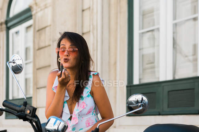 Красивая женщина в солнцезащитных очках, надевающая яркую помаду, глядя в зеркало мотоцикла на улице — стоковое фото