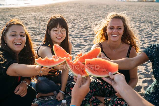 Un groupe d'amis sur la plage rassemblent leurs morceaux de pastèque — Photo de stock