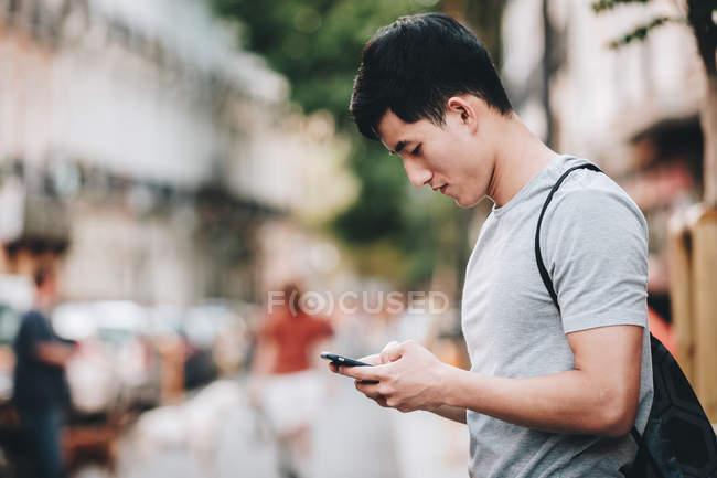 Seitenansicht eines asiatischen Mannes im T-Shirt, der auf einer belebten Straße herumsurft und sich umsieht — Stockfoto