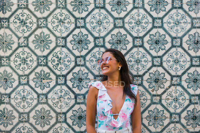 Peaceful gorgeous woman in trendy outfit and shiny sunglasses standing beside tiled exotic wall on scenic street — Stock Photo