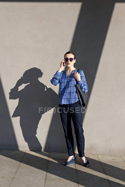 Attractive female manager in blue checkered shirt and sunglasses talking on smartphone and looking away — стокове фото