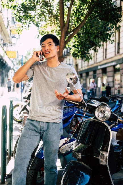 Positive casual asian man speaking on smartphone and gesturing while standing by motorcycle on sunny street — стокове фото