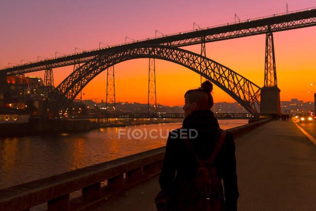 Vista posteriore dell'irriconoscibile turista donna che cammina vicino all'argine della città vicino al ponte durante il tramonto a Oporto, Portogallo — Foto stock