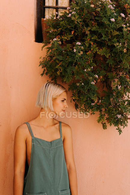 Bella giovane femmina con i capelli biondi corti guardando lontano e appoggiata al muro mentre in piedi su sfondo rosa sfocato — Foto stock