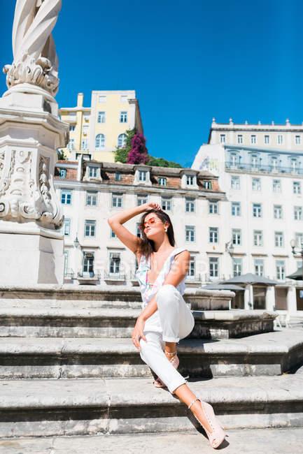 Belle femme détendue en tenue tendance assise sur un escalier en pierre dans une rue pittoresque — Photo de stock