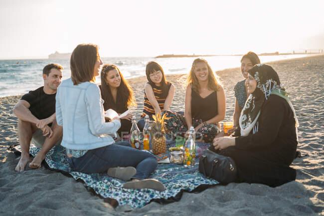Eine Gruppe von Freunden picknickt am Strand, die Sonne hinter sich — Stockfoto