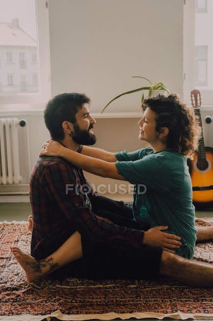Side view of tender couple in casual clothes cuddling and smiling while sitting on carpet on floor at home — Stock Photo