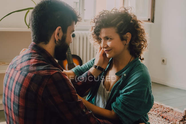 Vista laterale di coppia tenera coccole e sorridente mentre si siede sul pavimento a casa e si tocca in faccia — Foto stock