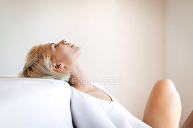 Side view of beautiful blond lady looking up and leaning on comfortable mattress against white wall at home — Stock Photo