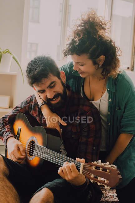 Tenera coppia allegra in abiti casual suonare la chitarra a casa — Foto stock