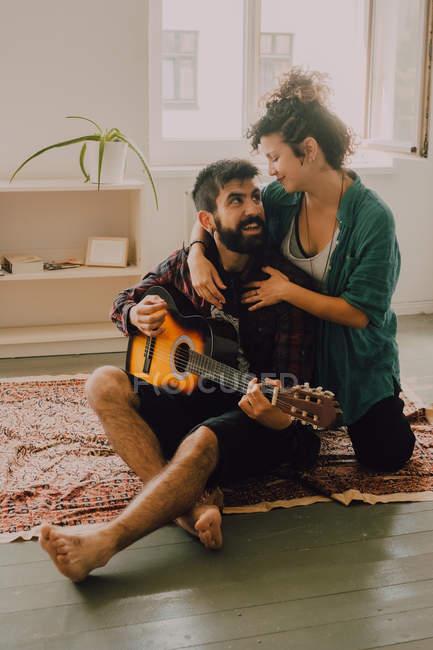 Zartes, fröhliches Paar in lässigem Outfit spielt zu Hause Gitarre — Stockfoto
