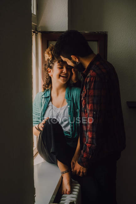Joyful casual couple smiling and hugging while leaning on window sill — Stock Photo