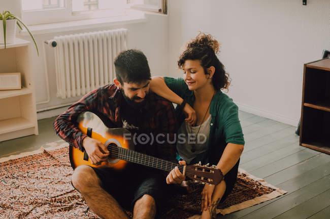 Allegro uomo e donna in abiti casual suonare la chitarra a casa — Foto stock