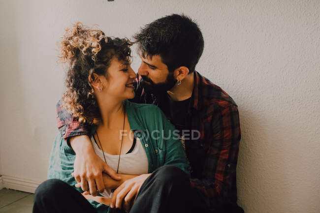 Joyful casual couple smiling and hugging while sitting on the floor and leaning on white wall at home — Stock Photo
