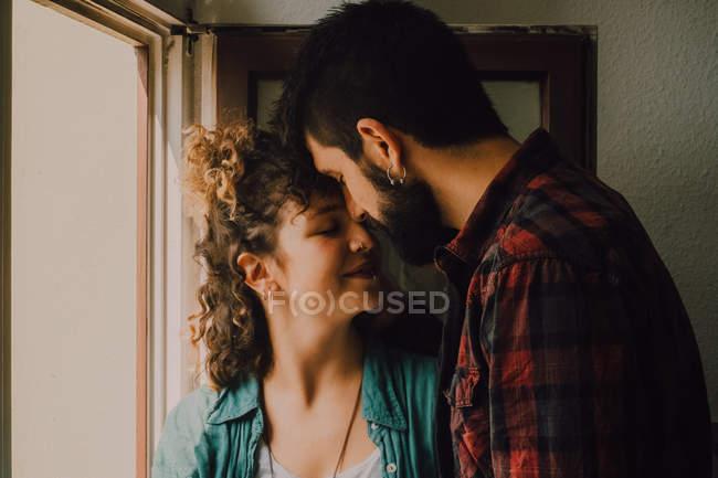 Joyeux couple occasionnel souriant et étreignant tout en s'appuyant sur le rebord de la fenêtre — Photo de stock
