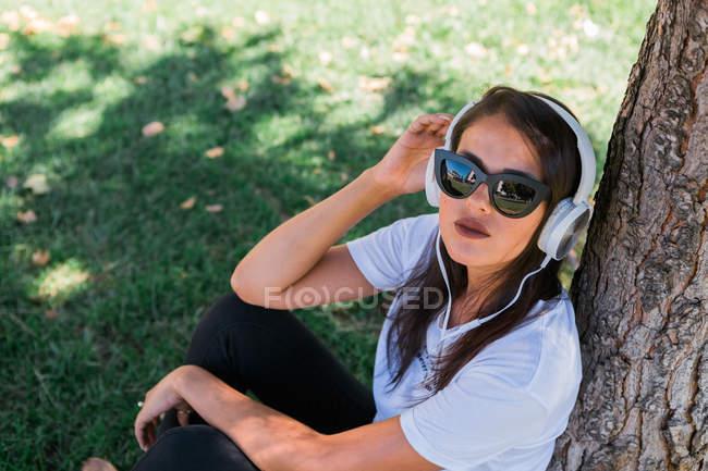 Mulher pacífica em óculos de sol e fone de ouvido ouvir música enquanto sentado na grama no parque — Fotografia de Stock