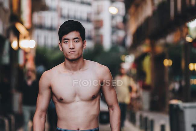 Juguetón asiático sin camisa chico de pie en la calle urbana en la luz del día - foto de stock