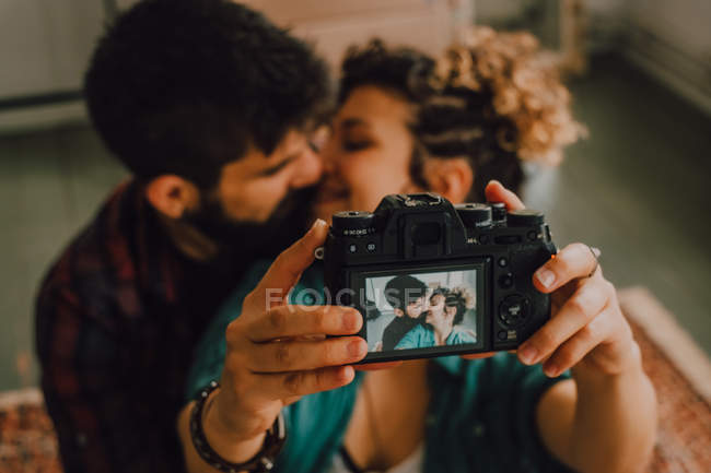 From above view of affectionate hipster couple hugging and taking selfie on camera while sitting at home — Stock Photo