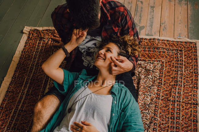 From above view of joyful casual couple smiling and hugging while lying on the floor at home — Stock Photo