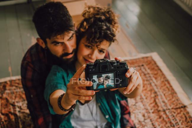 Сверху вид ласковой хипстерской пары, обнимающей и делающей селфи с фотокамерой, сидящей на полу дома — стоковое фото
