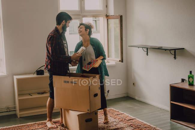 Couple Hipster déballant les boîtes ensemble en se tenant pieds nus dans une pièce légère — Photo de stock