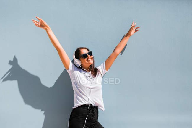 Красивая женщина в повседневной одежде и наушники на шее стоя с поднятыми руками у синей стены здания на городской улице — стоковое фото