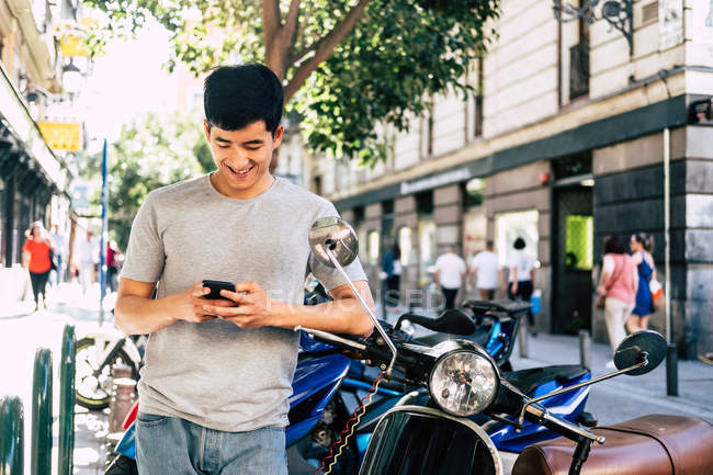 Positive casual asian man using smartphone while standing by motorcycle on sunny street — стокове фото