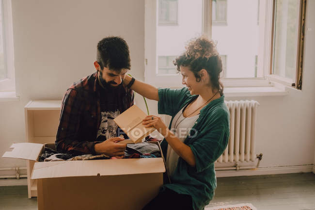 Cheerful couple laughing while sitting next to opened cardboard boxes in modern apartment — Stock Photo