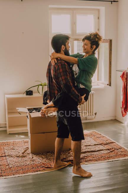 Вид сбоку влюбленной пары, обнимающейся и несущейся впереди, стоя рядом со стопкой картонных коробок дома — стоковое фото
