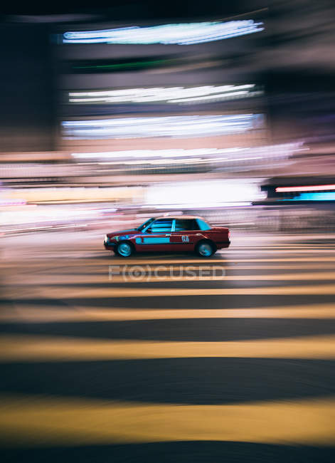 Long exposure shot of taxi car driving down striped city road in unfocused lights — Stock Photo