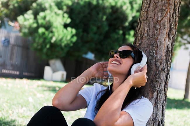 Donna pacifica con occhiali da sole e cuffie che ascolta musica mentre siede sull'erba nel parco — Foto stock