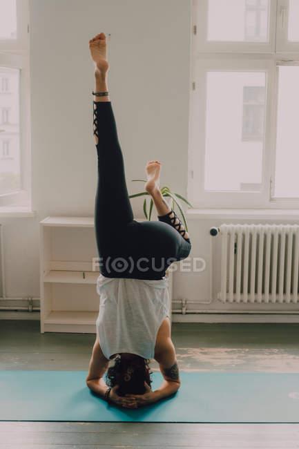 Задний вид на женщину в активной спортивной и делать стойку на голове на полу в квартире — стоковое фото