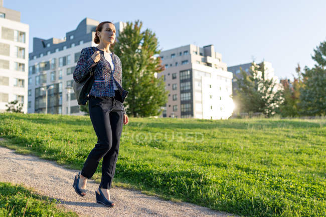 Full length businesswoman with bag walking along path near green lawn on sunny day in city park — Fotografia de Stock