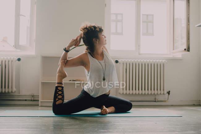 Женщина в активной одежде растягивается на коврике дома — стоковое фото