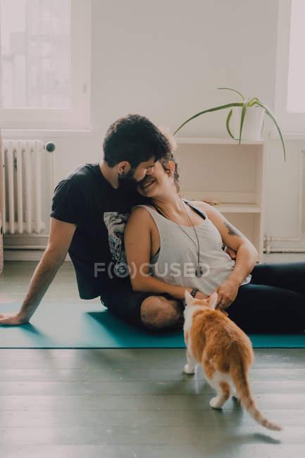 Вид сбоку нежной пары, которая обнимается и целуется, сидя на полу рядом с имбирной кошкой дома — стоковое фото