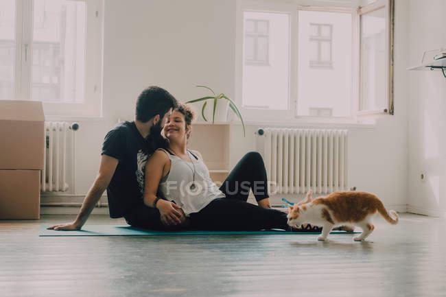 Вид сбоку нежной пары, сидящей на полу рядом с имбирной кошкой дома — стоковое фото