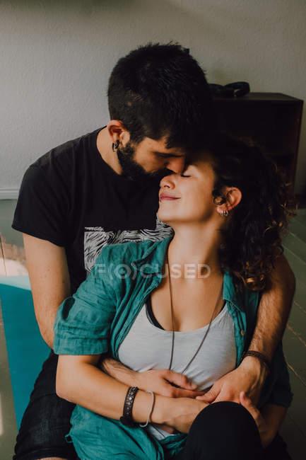 Casal afetuoso em trajes casuais beijando e abraçando enquanto descansa no apartamento moderno — Fotografia de Stock