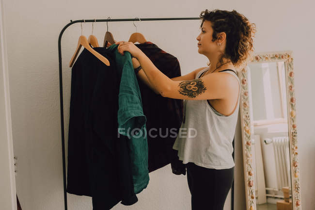 Side view of casual woman hanging shirts on hangers while standing barefoot in minimalistic room — стокове фото
